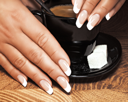 Female hands with a new manicure hold a cup of coffee. Stok Fotoğraf