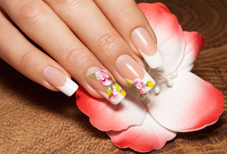Female hand with art nail manicure, against a flower background.