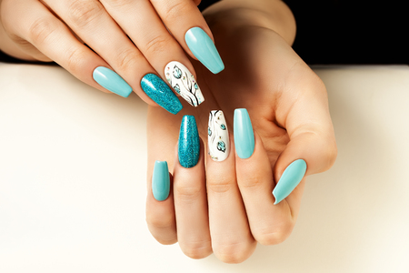 Blue female nails elongated with a design.