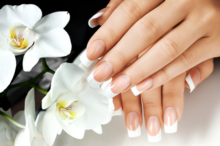 Female hands with white nails on background of white flowers. Stok Fotoğraf