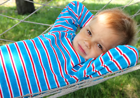 A young boy in a sentimental mood lies in a hammock.