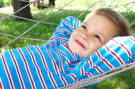 A boy in a hammock is smiling dreamily looking up.
