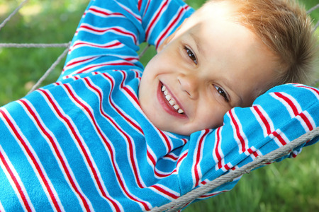 A young boy in a good mood lies in a hammock.