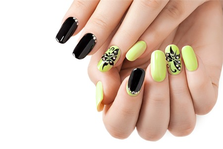Female manicure. Black and yellow long nails.