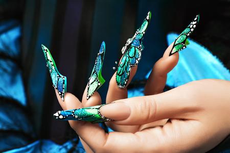 Hand des Mädchens Weibliche Maniküre Lange gefärbte Acrylnägel.