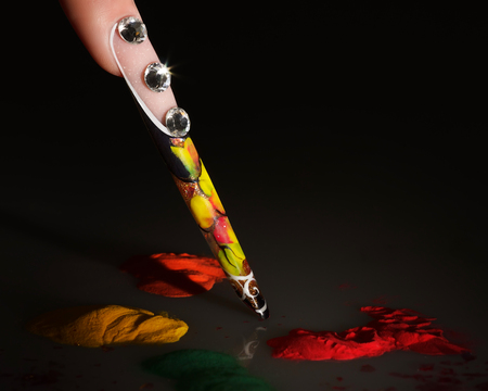 The girl's finger. Female manicure. Acrylic Powder. Long colored acrylic nails on a dark background. 写真素材