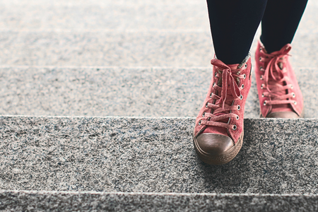 progressing: Woman legs in black leggings and pink sneakers climbing stairs outdoor
