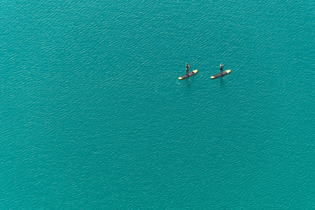 Aerial view of two unidentified stand up paddle boarders on the lake