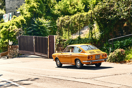 Young man driving yellow vintage Fiat 850 Sport Coupe released circa 1970 in Italy.