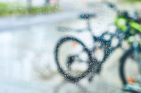 View of parked bicycles through the wet window glass with drops of water