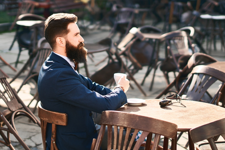 Young stylish businessman is drinking coffee in the morning cafe Stock Photo