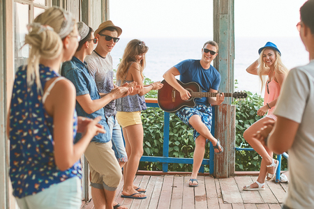 Friends hanging out on vacation at an old wooden cabin porch by the sea while one of them is playing guitar and others are giving him a round of applause 版權商用圖片