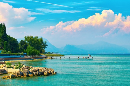 Beautiful landscape view of summer lake Garda in Italy with turquoise water and amazing pink evening clouds Stock Photo