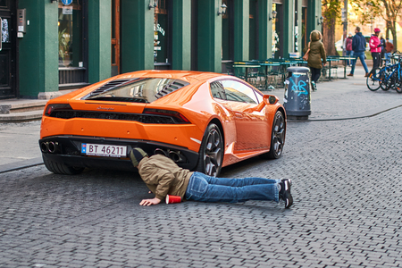 Orange Lamborghini Huracan LP 580-2 Spyder car released circa 2016 in Italy parked on the street causing a great interest among passers by. Editorial