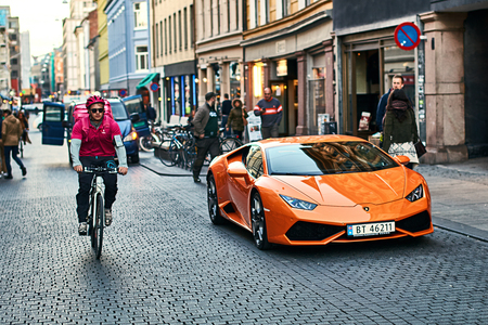 Orange Lamborghini Huracan LP 580-2 Spyder car released circa 2016 in Italy parked on the street with a bicycle courier passing by.