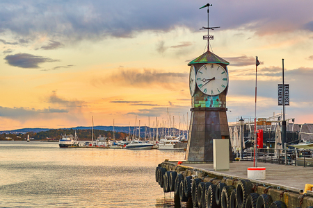 Clock tower on Aker Brygge Dock at the waterfront with marina on background. Editorial