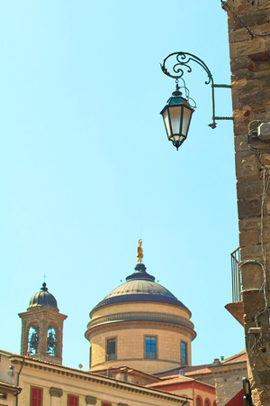 Street landern in Bergamo, Italy with the Bell tower and dome of Cathedral, Upper Town, on the background