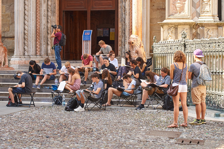 Architecture students drawing architectural details during en plein air assignment near Basilica of Santa Maria Maggiore in historical Upper Town