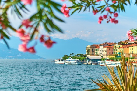 Beautiful sunny summer view of Bellagio town at lake Como in Italy with blooming nerium oleander flowers, ships and boats