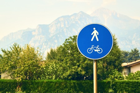 Pedestrian and bicycle road sign on mountains background Stock Photo