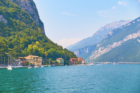 Steep alpine banks of beautiful lake Como with parked boats and yachts near village of Pare, Italy
