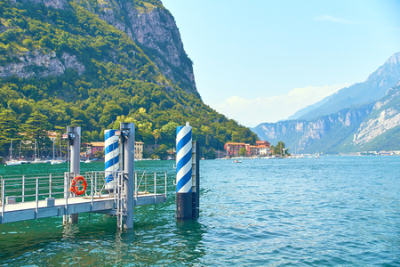 Pier or quay for ships and boats on steep alpine banks of beautiful lake Como with parked boats and yachts near village of Pare, Lombardy, Italy