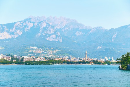 Beautiful summer view of the city of Lecco in Italy on the shore of lake Como with visible bell tower of the church of San Nicolo Stock Photo