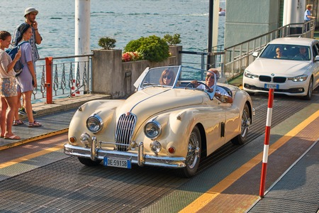 Happy man drives out his vintage beige Jaguar XK120, a sports car manufactured by Jaguar circa 1950, from the ferry boat at lake Como Editorial