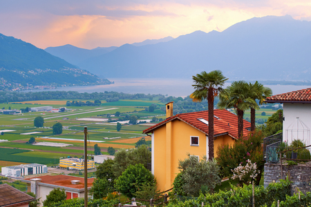 View of rural Southern Switzerland with houses, farms, vineyards, alps mountains and Lake Maggiore Stock Photo