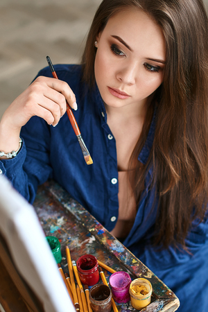 Young beautiful girl, female artist painter thinking of a new artwork and ready to make the first brushstroke Stock Photo