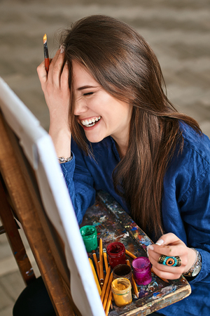 Young beautiful girl, female artist painter smiling, laughing and making a facepalm gesture thinking of a new artwork with a brush in her hand
