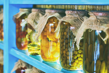 Glass jars covered with burlap fabric with different homemade canned food, preserved vegetables on wooden shelves