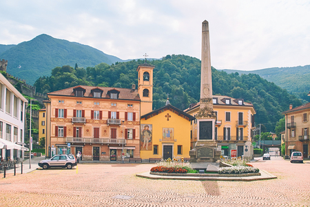 Beautiful view of Piazza Indipendenza or Independence Square in Bellinzona, Switzerland with an obelisk erected in 1803 to mark the centenary of the Act of Mediation and Sasso Corbaro castle on the hill