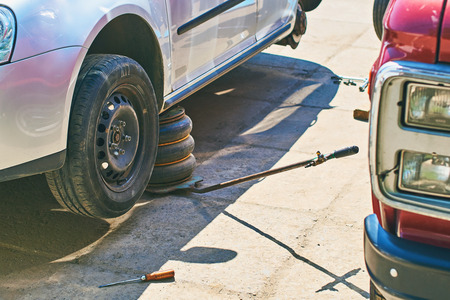 Changing wheels or tires on an grey automobile at an outdoor car service with old jack