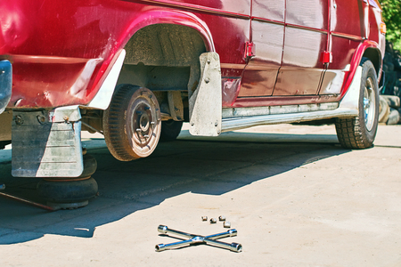 Changing a wheel or tire on an old vintage red van at outdoor car service