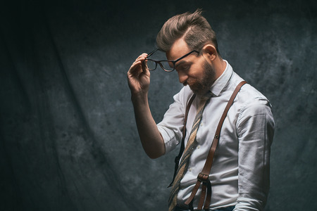 Young tired stylish hipster with cool hairstyle and beard dressed in white shirt and suspenders takes off his glasses Stock Photo