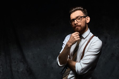 Young stylish hipster with cool hairstyle and beard dressed in white shirt and suspenders is thinking of a new creative idea