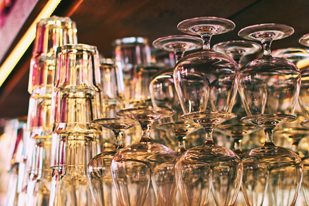 Different glassware and drinkware such as glasses and cognac snifters at a bar
