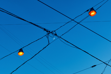 View of new moon crescent through the electric wires on the street with lights which have just been lit Stock Photo
