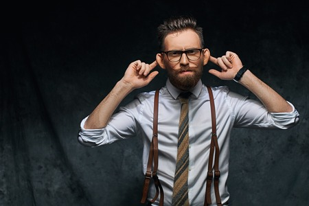 Young stylish hipster businessman or manager is stretching his ears, imitating monkey in a funny way or pretending not hearing somebodys speech or other sounds Stock Photo