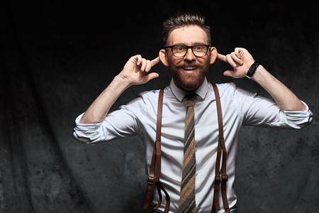 Young stylish businessman or manager holds his necktie in hand as if he decided to hang himself on it conceptually showing high level of stress and overwork