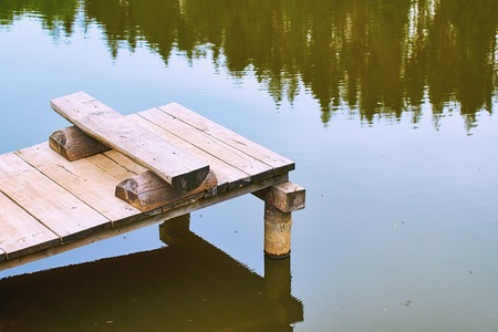 Cozy fishing bench on a wooden pier at the shore of a calm pond or lake in summer nountains