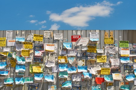 Bulletin board on the metal fence with colourful messages on the street