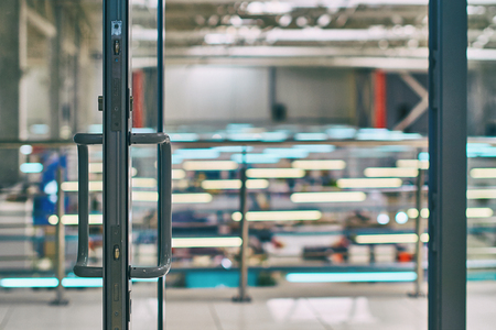 Open door in the modern office or shopping center in grey colors with bokeh background Stock Photo