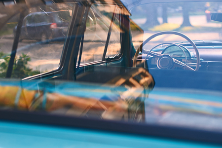 Interior of an old blue vintage car parked on the evening street at sunset in calm urban city setting