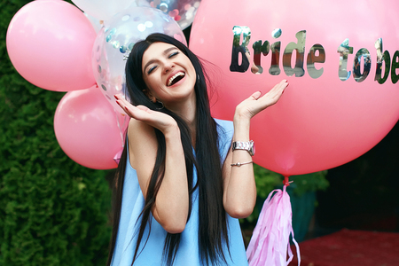 Happy young beautiful brunette bride to be with dark hair and silver crown smiling and spreading out her hands in joy on bachelorette pink party balloon background