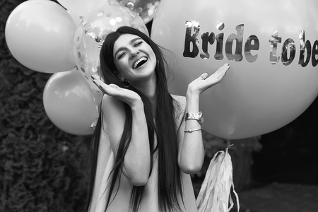Happy young beautiful brunette bride to be with dark hair and silver crown smiling and spreading out her hands in joy on bachelorette party balloon background in black and white