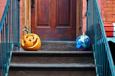Carved Halloween pumpkins or jack olantern on the doorstep in Brooklyn
