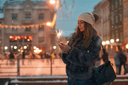 Beautiful young woman in fur coat holding a sparkler enjoys winter Christmas mood in old snowy European city with outdoor skating rink on background