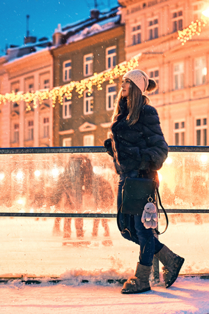 Beautiful young woman in fur coat stands by a skating rink border on old snowy European city background